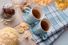 两个杯子在一块亚麻制蓝色餐巾的热的茶 干八仙花属,柠檬,栗子,桂香 图库摄影