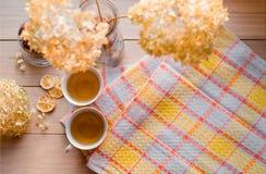 两个杯子在一块亚麻制黄色餐巾的热的茶 干八仙花属,柠檬,栗子,桂香 题字的地方 库存图片