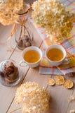 两个杯子在一块亚麻制黄色餐巾的热的茶 干八仙花属,柠檬,栗子,桂香 题字的地方 免版税库存照片