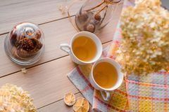 两个杯子在一块亚麻制黄色餐巾的热的茶 干八仙花属,柠檬,栗子,桂香 题字的地方 图库摄影