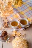 两个杯子在一块亚麻制黄色餐巾的热的茶 干八仙花属,柠檬,栗子,桂香 库存图片