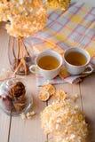 两个杯子在一块亚麻制黄色餐巾的热的茶 干八仙花属,柠檬,栗子,桂香 免版税库存图片