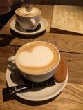 两个杯子在一张木桌上的热奶咖啡与泡沫的心脏和饼干 库存图片