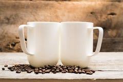 两个杯子在基于烤咖啡豆的阳光下 库存照片
