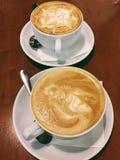 两个杯子在桌上的可口热奶咖啡 库存照片