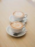 两个杯子在桌上的热奶咖啡 免版税库存照片