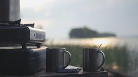 两个杯子在气体旅游板材的热的茶反对一个湖的背景有早晨太阳的强光的 行动  免版税库存图片