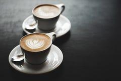 两个杯子在黑桌上的热奶咖啡 免版税库存照片