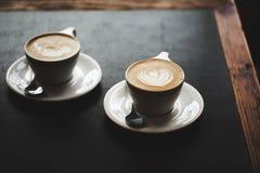 两个杯子在黑桌上的热奶咖啡 库存照片