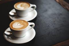 两个杯子在黑桌上的热奶咖啡 免版税库存图片