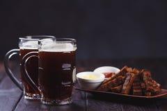 两个杯子壮健和嘎吱咬嚼的黑麦多士,供食用蕃茄和 免版税库存照片