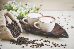 两个杯子新近地酿造的,泡沫的热奶咖啡 溢出的咖啡粒、巧克力和蔗糖 免版税库存照片