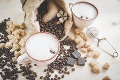 两个杯子新近地酿造的,泡沫的热奶咖啡 溢出的咖啡粒、巧克力和蔗糖 图库摄影