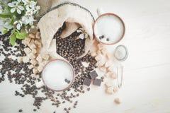 两个杯子新近地酿造的,泡沫的热奶咖啡 溢出的咖啡粒、巧克力和蔗糖 库存照片