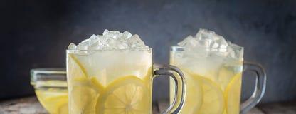 两个杯子柠檬水和冰块面包屑在木桌后面 库存照片