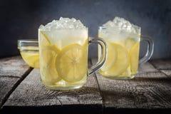 两个杯子柠檬水和冰块面包屑在木桌背景 免版税库存图片