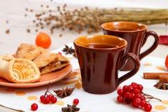 两个杯子棕色黏土用茶在一张白色亚麻布餐巾 黄油曲奇饼用果子果酱和蛋糕用酸奶干酪在r 库存图片