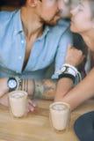 两个杯子热奶咖啡和亲吻夫妇在咖啡馆 免版税图库摄影