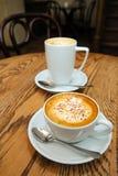 两个杯子热奶咖啡和拿铁 免版税库存照片