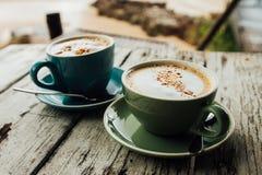 两个杯子热奶咖啡在木桌上的咖啡立场 绿色和蓝色杯子咖啡 免版税库存图片
