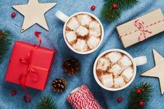两个杯子热的可可粉或巧克力用蛋白软糖、礼物盒、圣诞节装饰和杉树在被编织的蓝色背景从上面 免版税库存照片