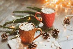 两个杯子热的可可粉用在土气木桌上的蛋白软糖与圣诞灯 库存图片