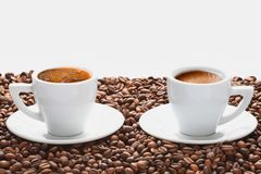 两个杯子热的咖啡用在白色背景的咖啡豆 免版税库存照片
