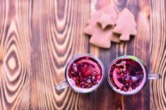 两个杯子红色被仔细考虑的藤用说谎在黑暗的木桌上的香料、柑橘水果和鲜美姜饼 顶视图 复制空间 免版税库存图片