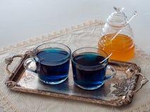 两个杯子蓝色蝴蝶豌豆开花茶、集合在一个银色盘子和一个瓶子蜂蜜 库存图片
