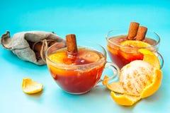 两个杯子被仔细考虑的酒用桂香和桔子在五颜六色的蓝色背景 免版税图库摄影