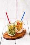 两个杯子被灌输的戒毒所饮食刷新的水-首先用黄瓜和柠檬,其次用柠檬和桃子 库存照片