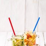 两个杯子被灌输的戒毒所饮食刷新的水-首先用黄瓜和柠檬,其次用柠檬和桃子 图库摄影