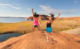 两个极度高兴女孩跳跃 免版税图库摄影