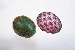 两个架线的复活节彩蛋被隔绝的绿色和桃红色 免版税库存图片