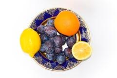 两个柠檬、桔子和李子在板材 免版税图库摄影