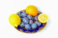 两个柠檬、桔子和李子在板材 免版税库存图片
