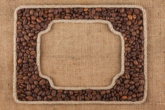 两个框架由绳索制成用咖啡豆在麻袋布 免版税图库摄影