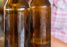 两个棕色瓶与小滴的啤酒蒸发了特写镜头,空 库存照片