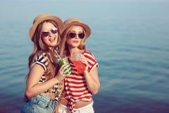 两个欧洲女孩获得乐趣在海滩的夏天 免版税库存图片
