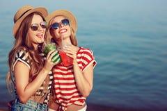 两个欧洲女孩获得乐趣在海滩的夏天 库存照片