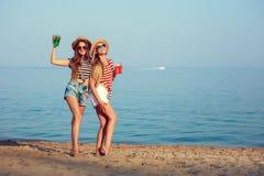 两个欧洲女孩获得乐趣在海滩的夏天 库存图片