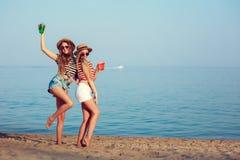 两个欧洲女孩获得乐趣在海滩的夏天 免版税库存照片
