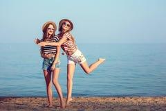 两个欧洲女孩获得乐趣在海滩的夏天 图库摄影