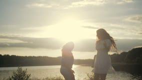 两个欧洲女孩在湖边在明媚的阳光下跳舞 牛仔裤穿戴的卷曲金发碧眼的女人 美丽的浅黑肤色的男人 股票视频