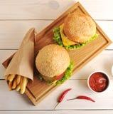 两个汉堡包用在一个纸袋和ketchu的油煎的土豆 库存照片