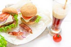 两个汉堡服务与杯在白色桌上的苏打 图库摄影