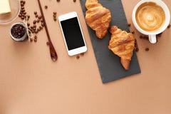 两个法国新月形面包企业早餐与智能手机的 库存照片