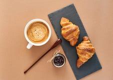 两个法国新月形面包早餐用果酱和咖啡 库存照片