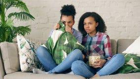 两个混合的族种卷曲女朋友坐在电视的长沙发和手表非常可怕电影和在家吃玉米花 库存照片