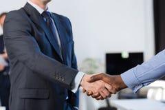 两个混合种族无法认出的商人震动手协议Coworking中心企业队工友 免版税库存照片
